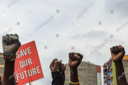 Residents of Mathare slum hold placards as they put their fist in the air as a sign of solidarity, during a protest against police brutality and killings that have been witnessed during security operations recently and in the past few years, in the streets of the Mathare slums in Nairobi, Kenya, 08 June 2020. According to a statement by the Independent Policing Oversight Body (IPOA), Kenyan police have been involved in the killing of 15 people as they enforced dusk to dawn curfew, since it was imposed by Kenyan President Uhuru Kenyatta in March 2020, as a preventive measure to curb the spread of the SARS-CoV-2 coronavirus, which causes the COVID-19 disease.
