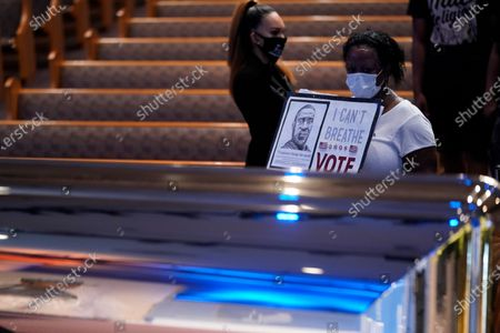 Stock Image of Mourner Vicki Irving, passes by the casket of George Floyd during a public visitation for Floyd at the Fountain of Praise church, in Houston
