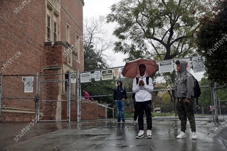 """Students wait outside of John Marshall High School after being let out early following an announcement of a district-wide closure caused by the coronavirus threat in Los Angeles. California's Department of Education plans to release a detailed how-to guide to safely reopen schools in the age of face masks and physical distancing. State Superintendent of Public Instruction Tony Thurmond says he'll release a new manual, titled """"Stronger Together: A Guidebook for the Safe Reopening of California's Public Schools"""