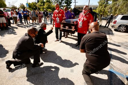 Pastors Dewayne Winrow and James Thomas, left to right, of Reseda Church of a Christ and Fluke Fluker, right, co-founder & president of Village Nation kneel as pall bearers carry a empty casket in memory of George Floyd as interfaith leaders, labor, people of color, immigrants, community members, and victims of police brutality, Black Lives Matter-LA begin a Vehicle procession to a memorial service in Downtown Los Angeles on Monday, June 8, honoring George Floyd and demanding justice for those killed by the hands of the police.