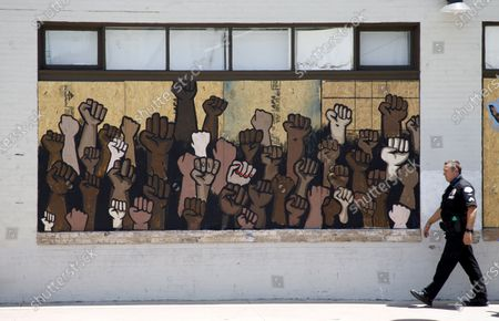 A Los Angeles Police Department LAPD officer walks past street art of raised fists on a boarded-up business near a demonstration protesting the police killing of George Floyd, in Los Angeles, California USA, 08 June 2020. Funeral services for George Floyd are ongoing in Houston, Texas as protests continue across the US.