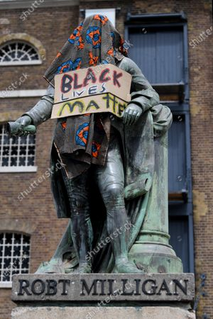 The statue of Robert Milligan, covered with a shawl and a Black Lives Matter poster, outside the Museum of London Docklands, London.  Milligan was a noted West Indian merchant, slaveholder and founder of West India Docks.