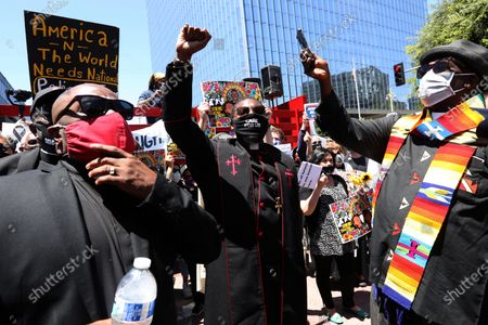 Stock Picture of The Rev. James Thomas, left, and Pastor Eddie Anderson, center, join hundreds at a Black Lives Matter-LA memorial service and funeral procession honor George Floyd and demanding justice for those killed by the hands of the police in Los Angeles on June 8, 2020. Interfaith leaders, labor, people of color, immigrants and victims of police brutality attended. The memorial services consisted of four funeral processions beginning in South Los Angeles, Long Beach, Orange County, and the San Fernando Valley. The processions converged in downtown Los Angeles at the crossing of 1st St and Broadway Blvd.. (Genaro Molina / Los Angeles Times)