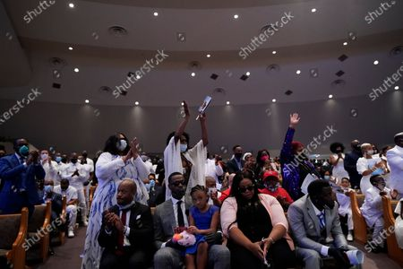 Sister of George Floyd, Zsa Zsa Floyd, both arms raised, attend the funeral service for Floyd at The Fountain of Praise church, in Houston