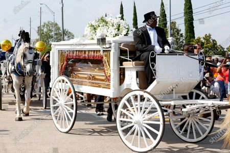 The casket carrying the remains of George Floyd arrives by horse-drawn carriage at Houston Memorial Gardens for his funeral in Pearland, Texas, USA, 09 June 2020. A bystander's video posted online on 25 May, appeared to show George Floyd, 46, pleading with arresting officers that he couldn't breathe as an officer knelt on his neck. The unarmed Black man later died in police custody and all four officers involved in the arrest have been charged and arrested.