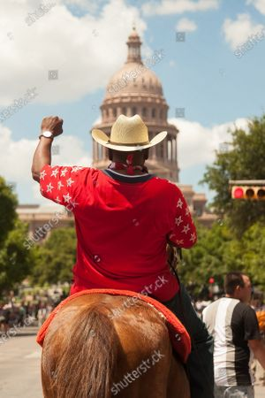 Black Cowboys make an entrance on horseback at the Capitol in Austin, TX, to protest the killing of George Floyd, who died at the hands of police.