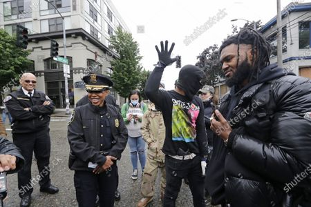 Seattle Police Chief Carmen Best, second left, shares a light moment with activists Raz Simone, right, and Keith Brown after a microphone fell as they talked near a closed Seattle police precinct, in Seattle, following protests over the death of George Floyd, a black man who was in police custody in Minneapolis. At left is Willie Barrington, Seattle Fire Department assistant chief. Under pressure from city councilors, protesters and dozens of other elected leaders who have demanded that officers dial back their tactics, the police department on Monday removed barricades near its East Precinct building in the Capitol Hill neighborhood, where protesters and riot squads had faced off nightly. Protesters were allowed to march and demonstrate in front of the building, and the night remained peaceful