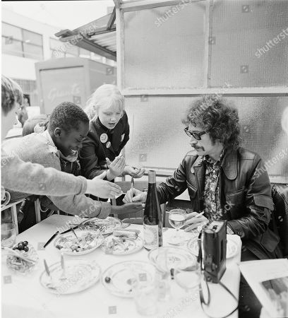 Peter Wyngarde signing autographs for children outside a restaurant.