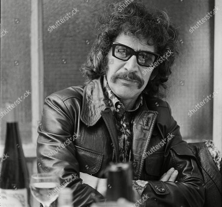 Peter Wyngarde relaxing outside a restaurant.