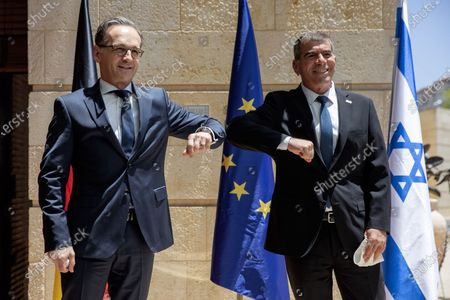 Israeli Foreign Minister Gabi Ashkenazi, right, welcomes his German counterpart Heiko Mass with a elbow bump due to the coronavirus outbreak, prior to their meeting in Jerusalem