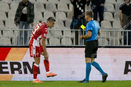 The referee gives yellow card to Milan Rodic of Crvena Zvezda