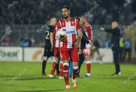 Milos Degenek of Crvena Zvezda takes the ball after stopping the game due the fans of both team launch torches into the fiel