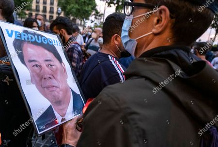 """A Nissan worker is seen carrying a portrait of Nissan CEO Makoto Uchida with writings reading """"executioner"""" during the protest. Workers of the Japanese car manufacturer have carried out a night march in Barcelona to visualize the more than 20,000 jobs at risk caused by the closure of the manufacturing plant in the Zona Franca (Barcelona)."""