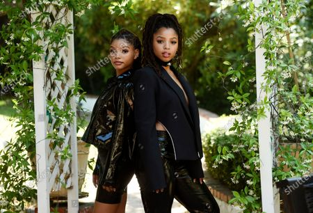 """Halle Bailey, left, and her sister Chloe Bailey, of the R&B duo Chloe X Halle, pose for a portrait in their backyard in Los Angeles to promote their latest release, """"Ungodly Hour"""