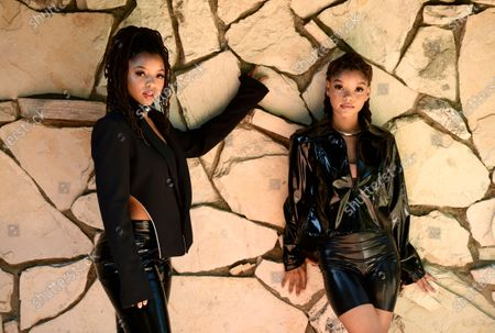 """Stock Picture of Chloe Bailey, left, and her sister Halle Bailey, of the R&B duo Chloe X Halle, pose for a portrait in their backyard in Los Angeles to promote their latest release, """"Ungodly Hour"""