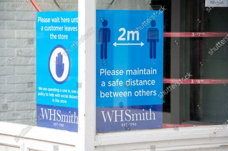 Stationery shop WH Smith in Windsor, Berkshire are getting ready to reopen and have put large social distancing signs in their windows. The Government has announced that non essential shops in England are allowed to reopen on 15th June 2020 following a relaxation in the lockdown rules