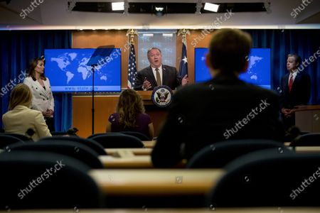 Secretary of State Mike Pompeo, center, accompanied by State Department spokeswoman Morgan Ortagus, left, and Sam Brownback, Ambassador at Large for International Religious Freedom, right, speaks during a news conference at the State Department in Washington