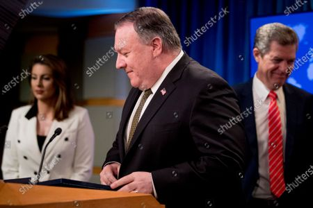 Secretary of State Mike Pompeo, accompanied by State Department spokeswoman Morgan Ortagus, left, and Sam Brownback, Ambassador at Large for International Religious Freedom, right, arrives for a news conference at the State Department in Washington