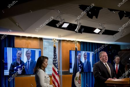 An image of Michael White, left, posing with U.S. special envoy for Iran Brian Hook, released after being detained for two years in Iran, is displayed behind Secretary of State Mike Pompeo, foreground, accompanied by State Department spokeswoman Morgan Ortagus, left, and Sam Brownback, Ambassador at Large for International Religious Freedom, right, as he speaks at a news conference at the State Department in Washington