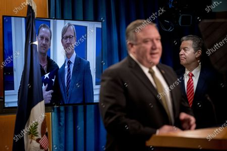 An image of Michael White, left, posing with U.S. special envoy for Iran Brian Hook, released after being detained for two years in Iran, is displayed behind Secretary of State Mike Pompeo, foreground, accompanied by Sam Brownback, Ambassador at Large for International Religious Freedom, right, as he speaks at a news conference at the State Department in Washington