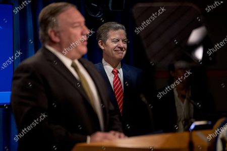 Secretary of State Mike Pompeo, left, accompanied by Sam Brownback, Ambassador at Large for International Religious Freedom, right, speaks during a news conference at the State Department in Washington