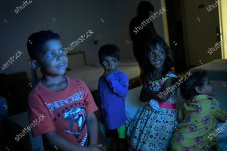 Stock Photo of Children from two families watch TV inside a hotel room that will serve as housing for the night, shortly after leaving the container they were living in with other homeless for months on a construction site for the unfinished Caracas-La Guaira tunnel alongside Baralt Avenue in Caracas, Venezuela, late . The city government, members of the United Socialist Party (PSUV) and National Guards escorted five families of 24 people living in two containers to temporary housing on Tuesday night, some of whom will be returned to their home states and others will enter into a government housing program, according to city officials on site. From left are Alejandro Ramirez Granadillo, age 6, Isaias Lopez, age 3, Daniela Lopez, age 5, and Daniela Ramirez Granadillo, age 2