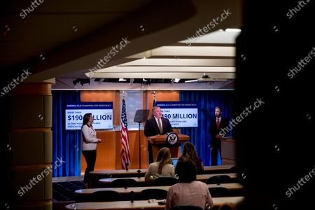 "Monitors display the words ""America is a Champion for Democracy More then 190 Million in New Humanitarian and Medical Assistance"" behind Secretary of State Mike Pompeo, accompanied by State Department spokeswoman Morgan Ortagus, left, and Sam Brownback, Ambassador at Large for International Religious Freedom, right, as he speaks during a news conference at the State Department in Washington"
