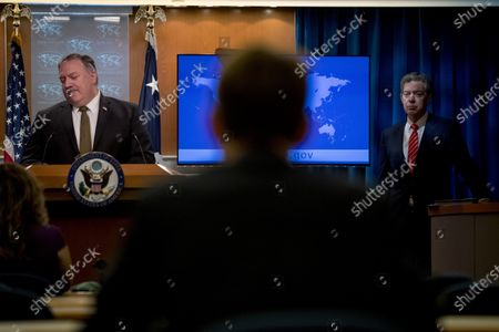 Secretary of State Mike Pompeo, left, accompanied by Sam Brownback, Ambassador at Large for International Religious Freedom, right, pauses while speaking at a news conference at the State Department in Washington