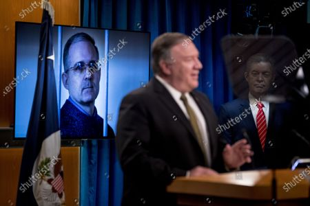 Stock Photo of An image of Paul Whelan, a former U.S. marine who was arrested for alleged spying in Moscow, is displayed behind Secretary of State Mike Pompeo, accompanied by Sam Brownback, Ambassador at Large for International Religious Freedom, right, as he speaks during a news conference at the State Department in Washington