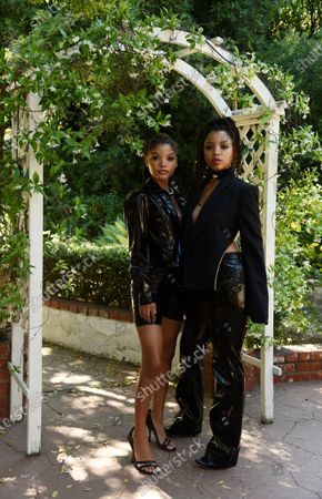 Halle Bailey, left, and her sister Chloe of the R&B duo Chloe X Halle pose together for a portrait in their backyard, in Los Angeles
