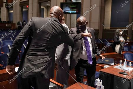 Ben Crump, civil rights attorney representing George Floyd's family, elbow bumps Paul Butler, law professor at Georgetown University Law Center, after a United States House Judiciary Committee hearing to discuss police brutality and racial profiling.
