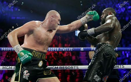 Tyson Fury, left, of England, fights Deontay Wilder during a WBC heavyweight championship boxing match in Las Vegas. An all-British world heavyweight title showdown between Anthony Joshua and Tyson Fury in 2021 is a step closer. Fury said, that an agreement has been reached with Joshua's camp on a two-fight deal between the current holders of the heavyweight belts