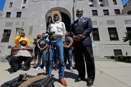 Tommie McGlothen, Sr., father of Tommie McGlothen, Jr., speaks to media outside the Caddo Parish Courthouse with attorney James Carter, right, and family members in Shreveport, La., . The family of the black Louisiana man who died in police custody after a videotaped altercation that shows police officers hitting and tasing him, demanded answers Wednesday and that the officers be held accountable