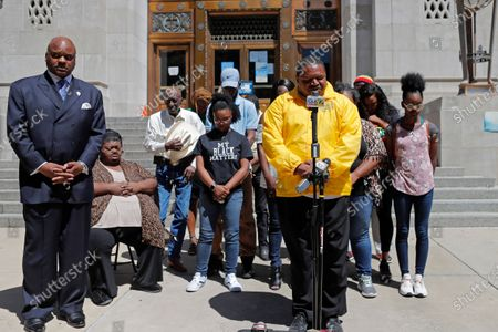 Stock Image of Pastor Linus Mays leads a prayer at the start of a news conference with family of Tommie McGlothen, Jr., outside the Caddo Parish Courthouse with attorney James Carter, left, in Shreveport, La., . The family of the black Louisiana man who died in police custody after a videotaped altercation that shows police officers hitting and tasing him Wednesday demanded answers and that the officers be held accountable