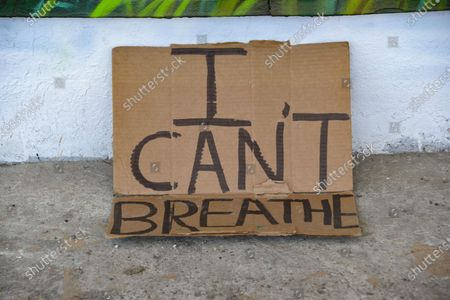 I can't Breathe is written on a piece of cardboard under a mural in Honor of Eric Garner and Geoege Floyd. A mural in Miami, honors Eric Garner and George Floyd. Both individuals lost their lives to police brutality and they are part of the Black Lives Matter movement.