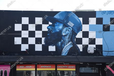 A mural in honor of Rapper Nipsey Hussle can be seen on top of a store in Wynwood.