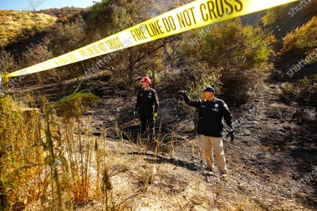 LAFD Arson investigators Robert Williams, left, and Joe Sanchez investigate the origin of the brush fire that broke out after midnight in the Sepulveda Pass threatening homes of Bel Air. Firefighters were able to stop forward movement of the blaze at about 50 acres.