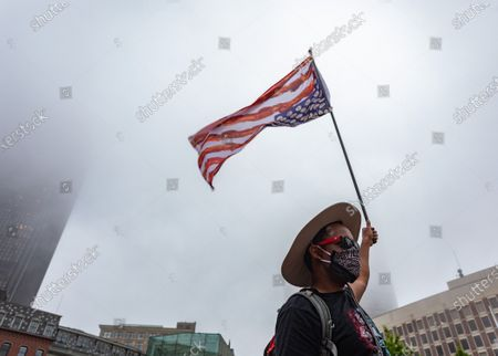 A protester raises an upside down American flag during a rally against police brutality and racism in Boston.