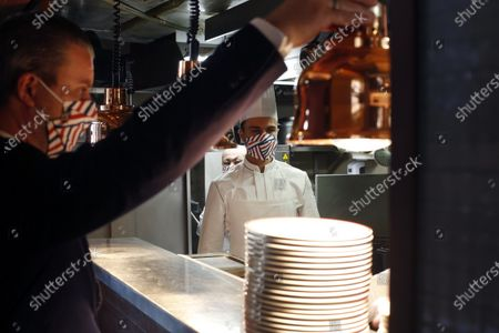 Waiter and a kitchen assistant wait for customers in the Alain Ducasse's restaurant « Allard », in Paris, . French Michelin-starred chef Alain Ducasse unveils virus-protection measures as he prepares to reopen his restaurants, including a new filtration system that works to stop virus particles from the air traveling to neighboring tables