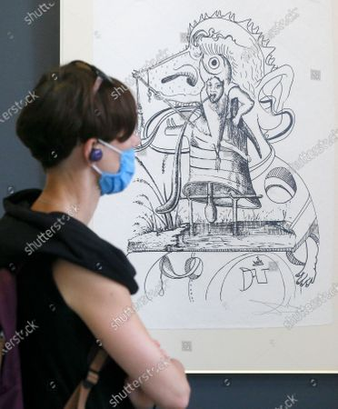 Visitor wearing a face mask to protect against coronavirus looks at a lithograph by Spanish artist Salvador Dali from a Kyiv-based private collection at an exhibition for sale in a city auction house in Kyiv, Ukraine, . The 25 lithographs based on XVI century French writer Francois Rabelais' Gargantua and Pantagruel and depicting human vices is estimated to be auctioned for thousands of US dollars