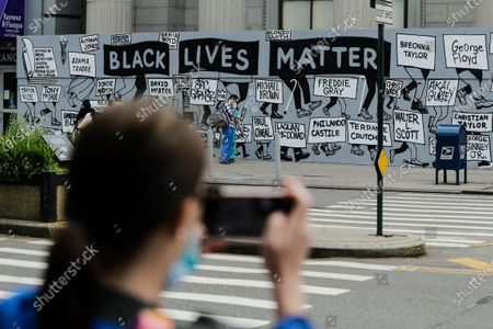 Stock Picture of Woman takes a photo with her smartphone as pedestrians pass a mural in Union Square calling for justice over the death of George Floyd, and to highlight police brutality nationwide, in New York. Floyd, a black man, died after he was restrained by Minneapolis police on May 25