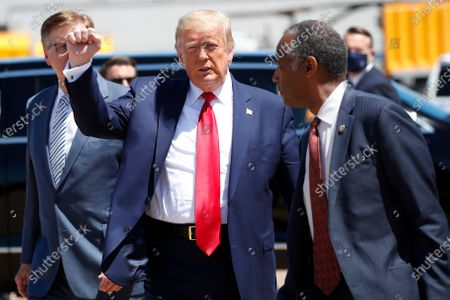 President Donald Trump walks with Texas Lt. Gov. Dan Patrick, left, and Housing and Urban Development Secretary Ben Carson as he arrives on Air Force One at Dallas Love Field, in Dallas