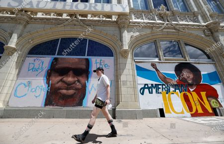 Pedestrian passes murals to honor George Floyd and former NFL quarterback Colin Kaepernick covering pieces of plywood used to shield windows in an empty storefront south of the State Capitol, in Denver