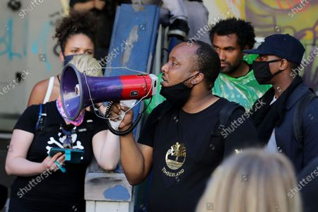 """Mark Henry Jr., center, a Black Lives Matter leader, speaks into a megaphone in a doorway of the Seattle Police Department East Precinct building, which has been boarded up and abandoned except for a few officers inside, in Seattle. The building is located in what is being called the """"Capitol Hill Autonomous Zone."""" Following days of violent confrontations with protesters, police have largely withdrawn from the neighborhood"""