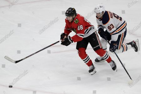"""Chicago Blackhawks right wing Patrick Kane, left, and Edmonton Oilers center Ryan Nugent-Hopkins chase the puck during the third period of an NHL hockey game in Chicago. Assuming everything goes according to plan and the final details are ironed out between the league and the players' union, the Blackhawks will play the Oilers in a best-of-five qualifier series for the playoff bracket. """"It's been a weird three months,"""" Kane said during a video conference call with reporters"""