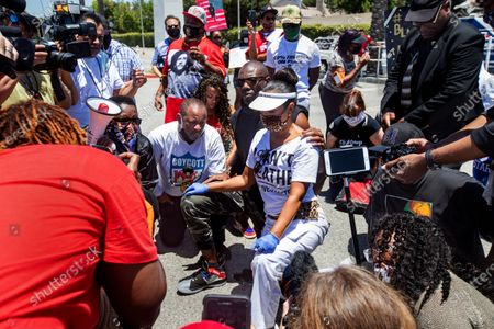 Retired NFL wide receiver and hall of famer Terrell Owens, center, (wearing sun glasses) takes a knee for 8 minutes and 46 seconds, in honor of George Floyd, during a protest across the street from Sofi Stadium in Inglewood, background, with others including actress LisaReye McCoy, to his right, and Najee Ali, of Project Islamic Hope, center, to his left. In addition to remembering George Floyd, who was held down by a police officer with a knee to his neck for 8 minutes and 46 seconds, that lead to his death, the protest was also against the NFL, demanding that the organization apologize to former NFL quarterback Colin Kaepernick. (Mel Melcon/Los Angeles Times)