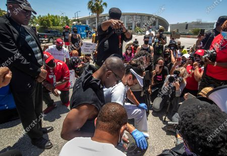 Stock Photo of Retired NFL wide receiver and hall of famer Terrell Owens, center, takes a knee for 8 minutes and 46 seconds, in honor of George Floyd, during a protest across the street from Sofi Stadium in Inglewood, background, with others including actress LisaReye McCoy, to his right, and Najee Ali, of Project Islamic Hope, center, back to camera. In addition to remembering George Floyd, who was held down by a police officer with a knee to his neck for 8 minutes and 46 seconds, that lead to his death, the protest was also against the NFL, demanding that the organization apologize to former NFL quarterback Colin Kaepernick. (Mel Melcon/Los Angeles Times)