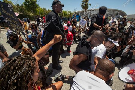 Stock Image of Retired NFL wide receiver and hall of famer Terrell Owens, 2nd from right, takes a knee for 8 minutes and 46 seconds, in honor of George Floyd, during a protest across the street from Sofi Stadium in Inglewood, background, with others including actress LisaReye McCoy, to his right, and Najee Ali, of Project Islamic Hope, center, back to camera. In addition to remembering George Floyd, who was held down by a police officer with a knee to his neck for 8 minutes and 46 seconds, that lead to his death, the protest was also against the NFL, demanding that the organization apologize to former NFL quarterback Colin Kaepernick. (Mel Melcon/Los Angeles Times)