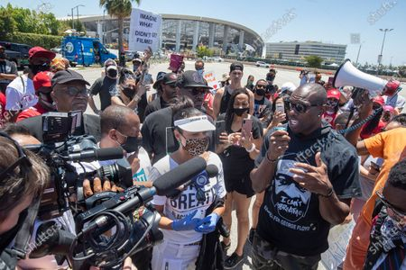 Stock Image of Retired NFL wide receiver and hall of famer Terrell Owens, right, addresses protesters outside of Sofi Stadium in Inglewood, background, demanding that the NFL apologize to former NFL quarterback Colin Kaepernick. At left in white visor is actress LisaReye McCoy. (Mel Melcon/Los Angeles Times)