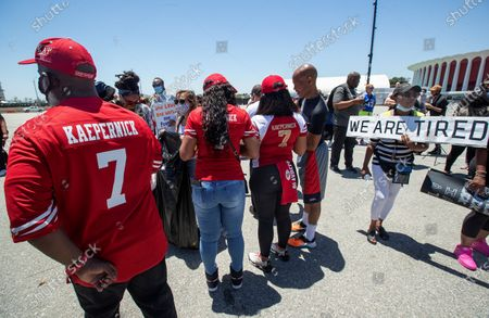Katie Fuller, 74, of Inglewood, right, holding sign, joins other protesters in the Forum parking lot, across the street from Sofi Stadium in Inglewood, background, demanding that the NFL apologize to former NFL quarterback Colin Kaepernick. The protesters also took a knee for 8 minutes and 46 seconds to remember George Floyd who who held down by a police officer with a knee to his neck for the same time and died as a result. (Mel Melcon/Los Angeles Times)